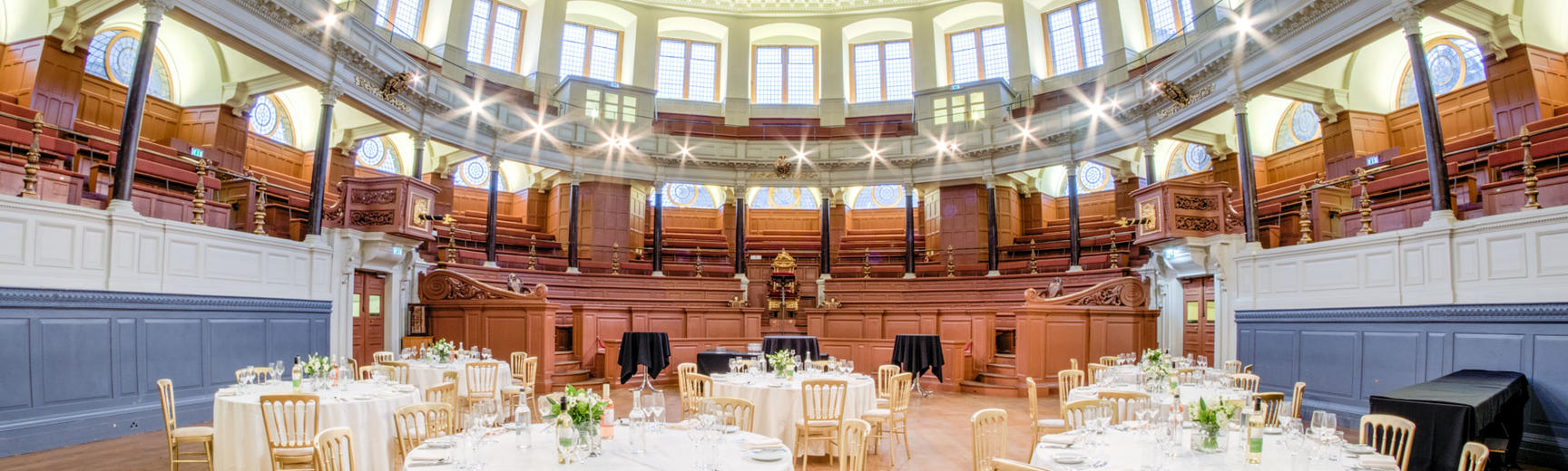 Photo of Sheldonian Theatre with tables and chairs set up for a wedding reception