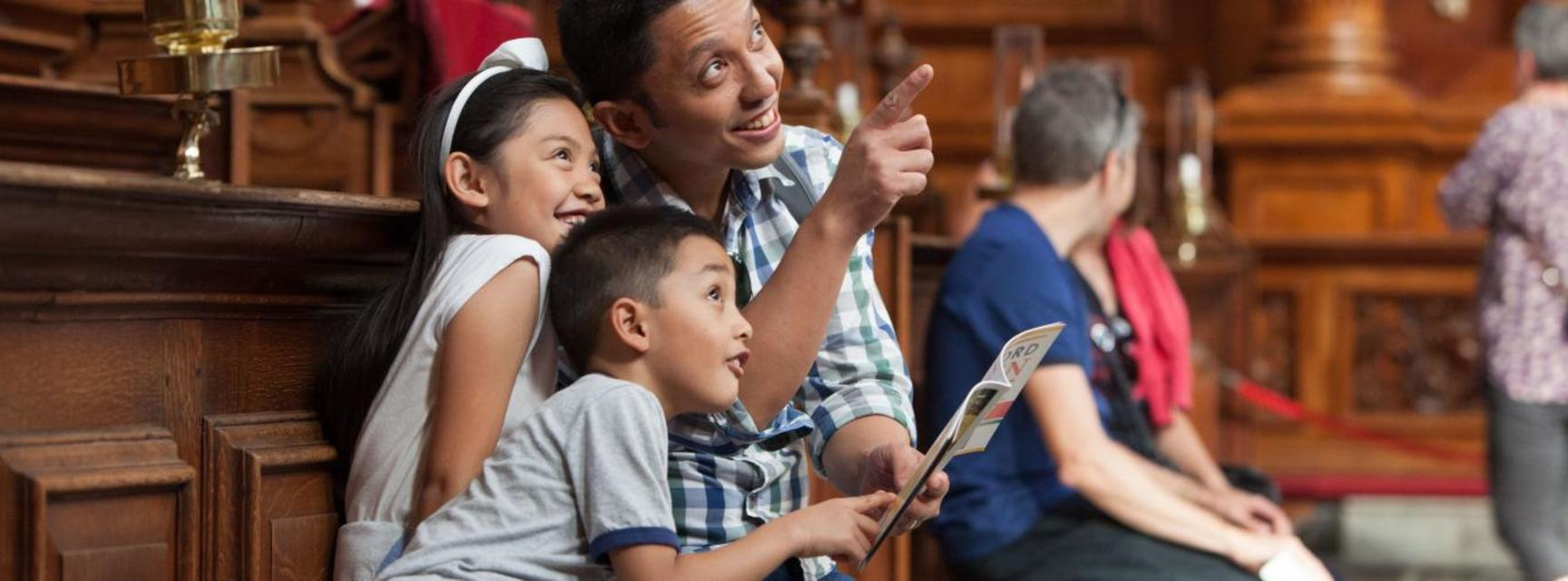 Photo of a family sitting inside the Sheldonian theatre, holding the Oxford Open Doors brochure and pointing, looking and smiling at the ceiling