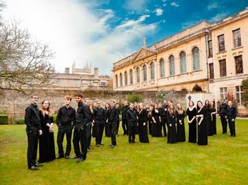 Photo of Queen's College Choir standing in the grounds of the college